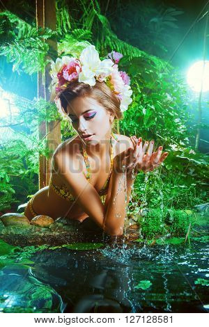 Tender beautiful girl in a flower wreath sits by a pond in the rainforest. Beauty, bodycare. Tropical vacation.