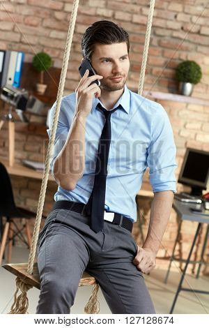 Young businessman sitting on swing in office, talking on mobilephone.