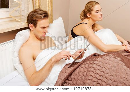 Couple in bed, man using tablet woman sitting bored
