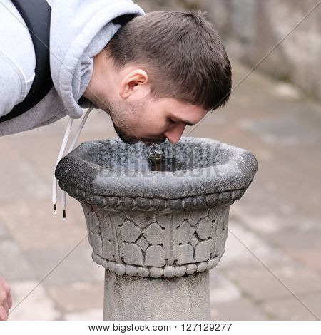Man drinking water from fountain at street