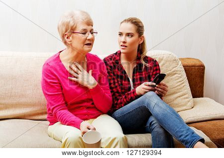 Mother with adult daughter watching sad movie