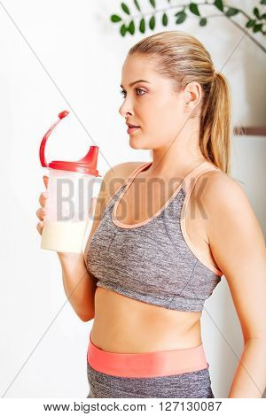 Young sporty woman drinking protein shake