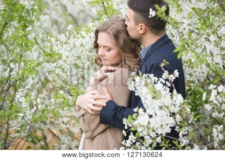 Young couple in love near the blossom apple tree