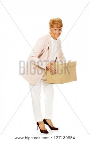 Smile elderly business woman holding cardboard box