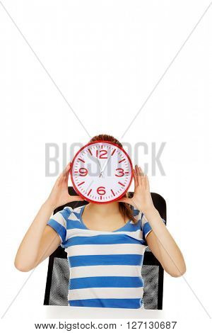 Teenage woman covering face with a clock