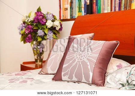 Little Table With A Vase With The Flowers And A Bed With Pillows