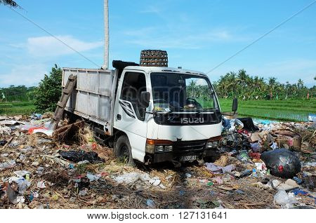 BALI INDONESIA - APRIL 10: A garbage truck dumps household rubbish and plastic bags next to contaminated rice fields and agricultural farmland at an illegal garbage dump on April 10 2016 in Ubud Bali Indonesia.