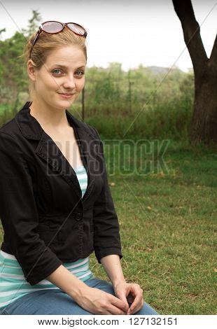 Photo of young woman sitting on grass
