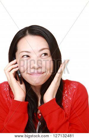 Japanese woman talking on smart phone pleased
