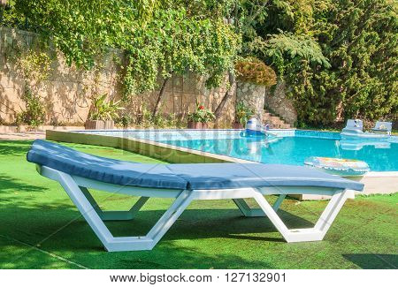 Beach chaise lounge by the pool in the park