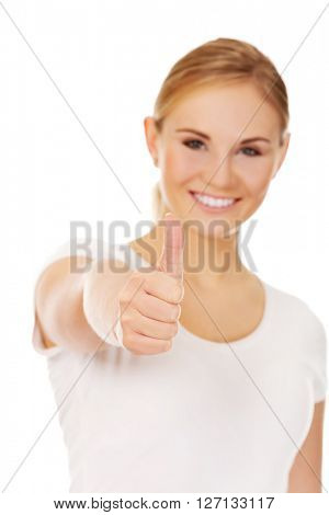 Young happy woman gesturing thumb up