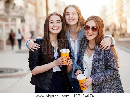 Three young women, best friends smiling at the camera.
