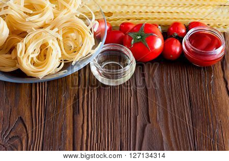 Two kinds of pasta from durum wheat and fresh tomatoes for making the sauce. Products on a wooden table with copy space.