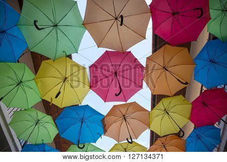 Many bright multicoloured umbrellas seen from above.