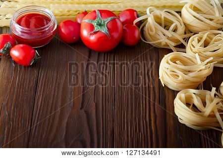Two kinds of pasta from durum wheat and fresh tomatoes, tomato sauce. Products on a wooden table with copy space.