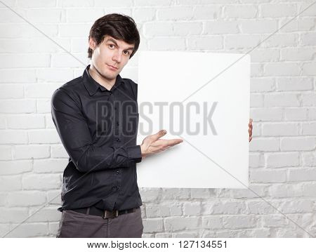 young man holding poster in brick room