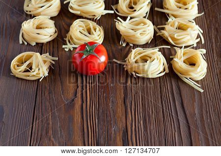 pasta from durum wheat and fresh tomatoes, tomato sauce. Products on a wooden table with copy space.