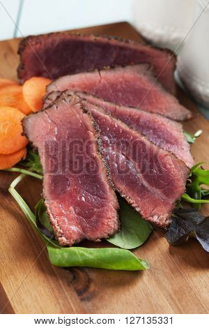Rare beef steak with carrot and fresh salad on wooden table