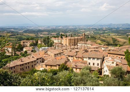 Tuscan village of San Gimignano Italy a medieval walled city and major tourist destination in Tuscany. Tiled rooftops a cathedral distant vineyards and hills with copy space in sky if needed.