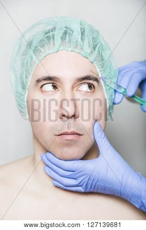 Doctor aesthetician makes hyaluronic acid rejuvenation beauty injections in the forehead of male patient in a green medical cap. Patient is looking on the doctor with mistrust and fear.