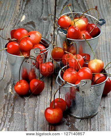 Three Tin Buckets Full of Ripe Sweet Maraschino Cherries closeup on Rustic Wooden background