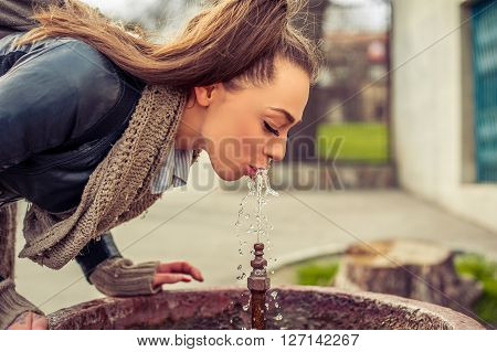 Woman drinking water from fountain. Young Woman drinking from a fresh water drink fountain