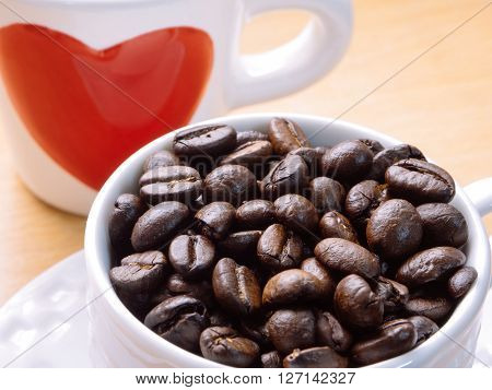 White cup of coffee beans with red heart on side of cup for love and valentine concept