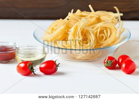 Products on a wooden table. Two kinds of pasta from durum wheat and fresh tomatoes for making the sauce.