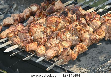 Grilling shashlik on barbecue grill. Barbecue maet on fire coal