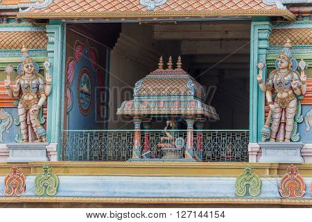 Trichy India - October 15 2013: Detail of the massive Rajagopuram of Ranganathar Temple. Focus on one opening protected by Dwarapalakas. Pastel colors pillars and statues. Lakshmi on lotus.