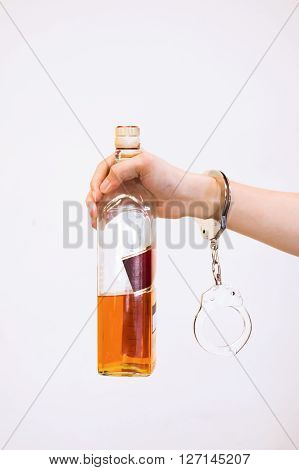 Man Hand Carrying Alcohol Drink With Handcuffs - Drunk Driving, Alcohol Addiction Effect Concept (fo