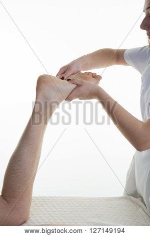 Man's Foot Reflexology By Brunette Female Therapist