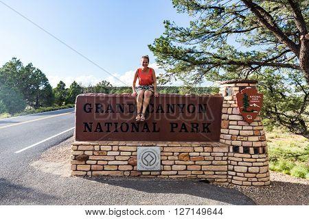 Girl sitting at Grand Canyon National Park entrance sign
