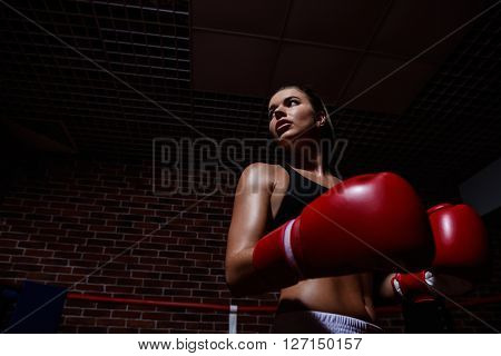 Young woman with gloves in boxing ring