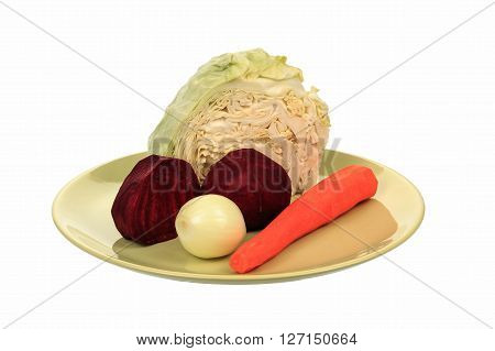 Beets cabbage onions carrots lay on a plate. Objects on a white background.