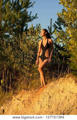 Woman in bikini over sand and trees