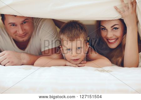 Young parents with their 6 years old little son dressed in pajamas are relaxing and playing in the bed at the weekend together, lazy morning.