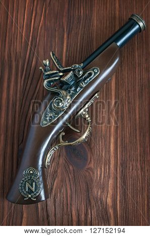 The old musket on a wooden background