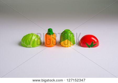 Assorted plastic vegetables on white background. Kids dream career concept.