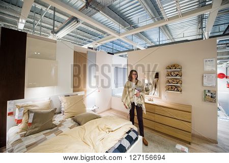 PARIS FRANCE - APR 12 2016: Elegant woman choosing bedroom furniture in the design store interior of IKEA furniture mall in PAris France