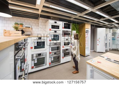 PARIS FRANCE - APR 12 2016: Woman buying kitchen furniture in the specialized showroom department