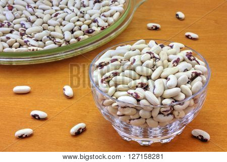 Colorful haricot beans in glass bowls on wooden background