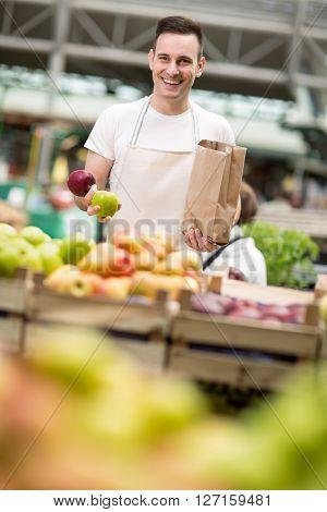 portrait salesman offers an apple at market store