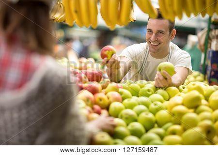 salesman offers an apple at street market