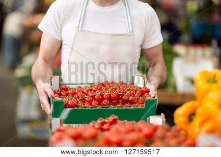 salesman holding organic cherry tomato at street market