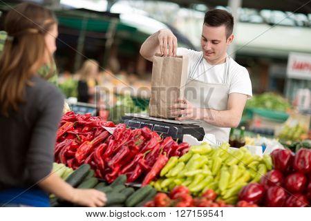 salesman measuring fresh vegetables at street market