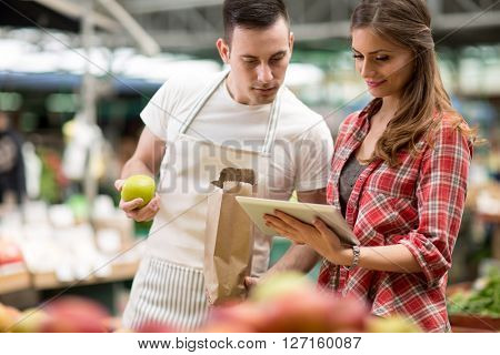 salesman and customer looking checking list on the tablet in the market