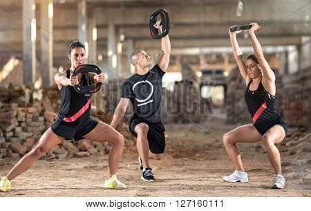 Group of young sporty people exercise with weights in unfinished building