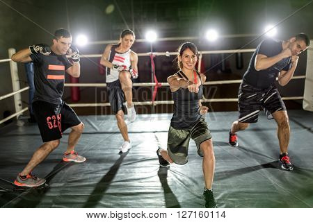 Young people practicing performer hit with hand in boxing ring