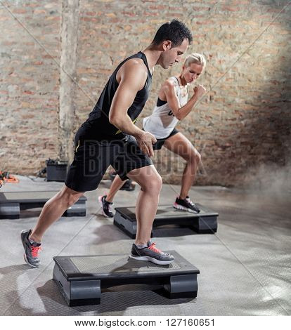 Sporty men train young woman  moves on stepper